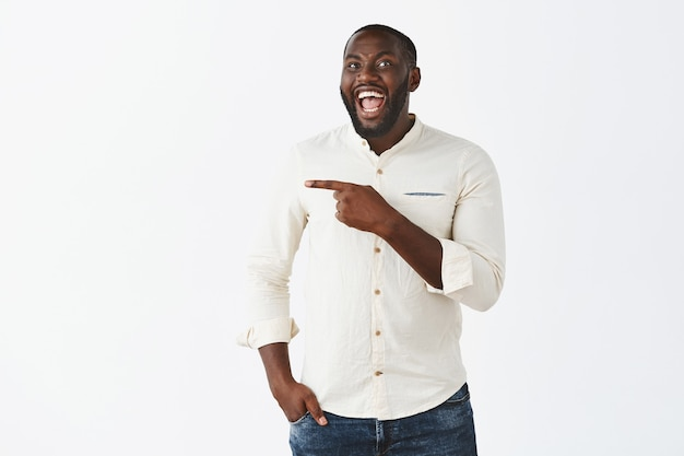 Knappe lachende jonge kerel poseren tegen de witte muur
