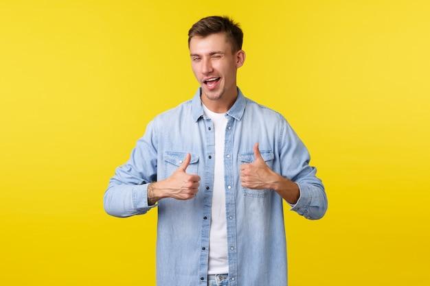 Knappe lachende jonge man duimen opdagen en knipogen. zelfverzekerde schattige kerel moedigt aan om te bewegen, goed werk te prijzen of goed gespeeld te zeggen. tevreden mannelijke klant laat positieve feedback achter.