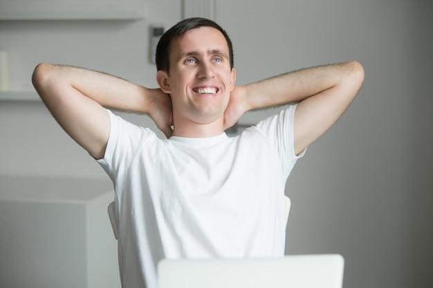 Knappe lachende jonge man uitsteken bij bureau met laptop