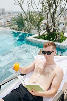 Knappe lachende jongeman glas vers sinaasappelsap drinken en lezen van een boek tijdens het ontspannen bij het zwembad