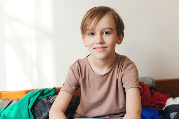 Knappe lachende jongen. jongen zit oh het bed met veel verspreide kleren.