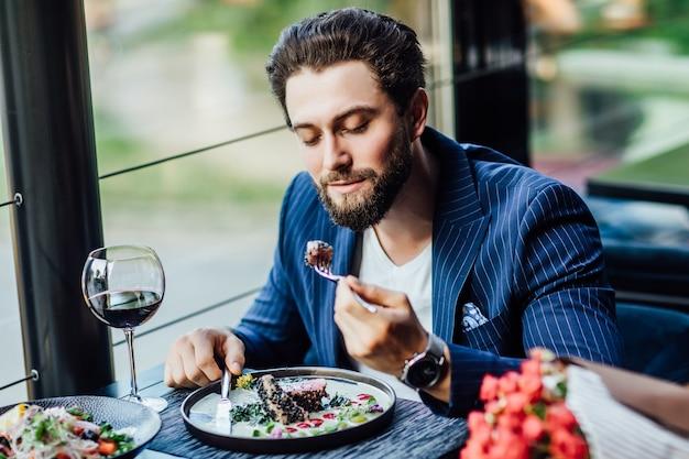 Knappe lachende man eet salade in restaurant en wachtende vrouw met boeket rozen