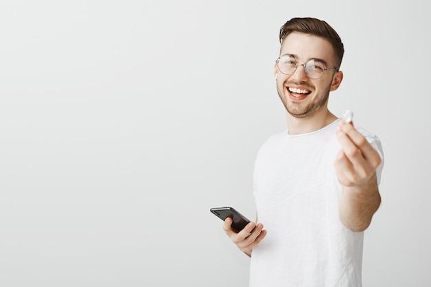 Knappe lachende man in glazen suggereert zijn oortelefoon om samen naar muziek te luisteren, waardoor je oortelefoon krijgt