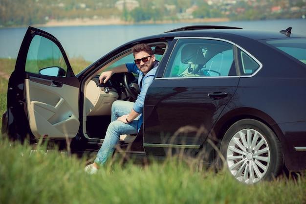Knappe lachende man in spijkerbroek, jas en zonnebril zit in zijn auto met geopende deuren aan de kant van de rivier.