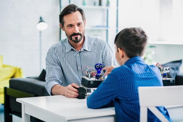 Knappe lachende man zit aan tafel met zijn zoon terwijl hij aan een robotproject werkt