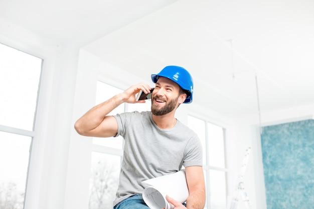 Knappe lachende reparateur of bouwer in helm praten met telefoon met tekeningen in het witte interieur