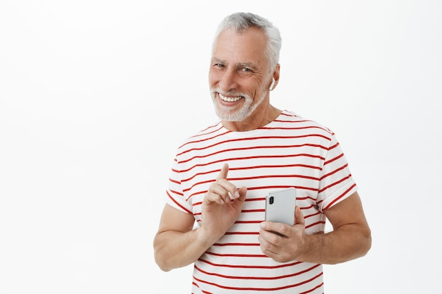 Knappe lachende volwassen bebaarde man met behulp van draadloze oortelefoons en smartphone