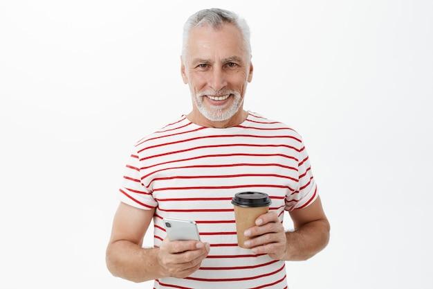 Knappe lachende volwassen man met koffie met behulp van mobiele telefoon