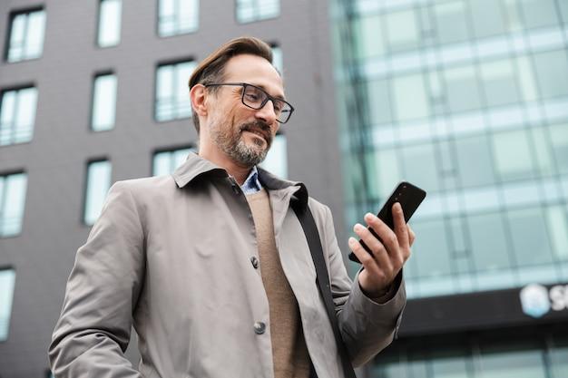 Knappe lachende zakenman in bril die mobiele telefoon gebruikt terwijl hij in de buurt van een glazen gebouw in stedelijk gebied staat