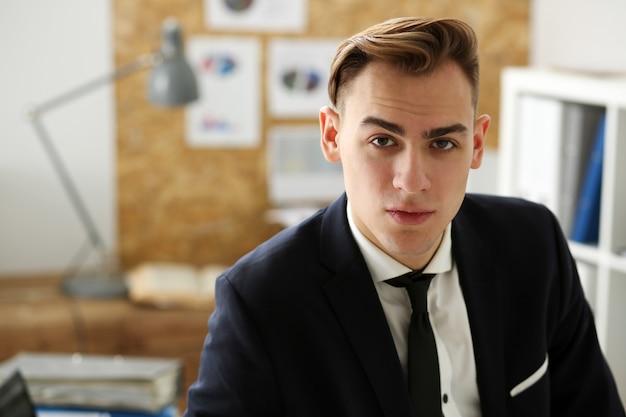 Knappe lachende zakenman in pak portret op werkplek kijken in de camera. bediende op werkruimte, beurs, baanaanbieding, gecertificeerde openbare accountant, concept van de interne belastingbeambte