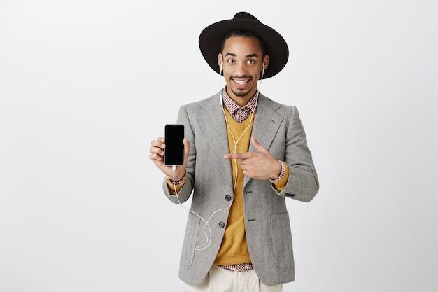 Knappe lachende zwarte man in pak en hipster hoed, muziek luisteren in oortelefoons, wijzende vinger op smartphonescherm