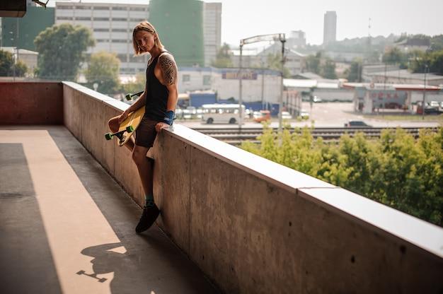 Knappe langharige man zittend op de borstwering met longboard