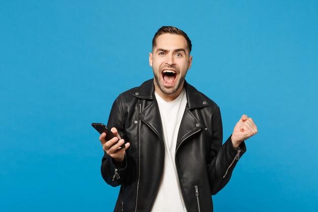Knappe leuke dolblij opgewonden jonge ongeschoren man in zwart lederen jas wit t-shirt met behulp van mobiele telefoon geïsoleerd op blauwe muur achtergrond studio portret. mensen levensstijl concept mock up kopie ruimte
