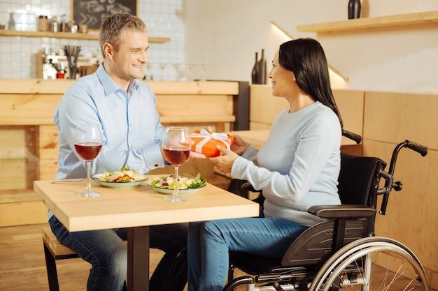 Knappe liefdevolle blonde man die lacht en een cadeau geeft aan zijn aantrekkelijke glimlachende gehandicapte vrouw tijdens een romantisch diner