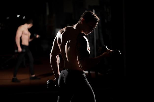Knappe macht atletische kerel bodybuilder doet oefeningen met halter. fitness gespierd lichaam op donkere achtergrond.