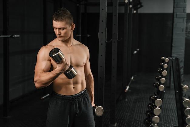 Knappe macht atletische man bodybuilder doen oefeningen met halter in een sportschool.