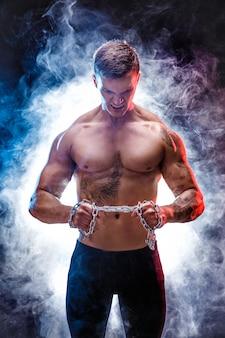 Knappe macht atletische man bodybuilder doen oefeningen met ketting, scheuren. fitness gespierd lichaam op donkere achtergrond. perfecte reu. geweldige bodybuilder, tattoo, poseren.