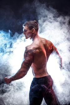 Knappe macht atletische man bodybuilder fitness gespierd lichaam op donkere rook scène
