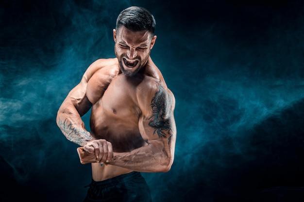 Knappe macht atletische man bodybuilder. fitness gespierd lichaam op donkere rookmuur. .