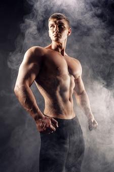 Knappe macht atletische man bodybuilder. geschiktheids gespierd lichaam op donkere rookachtergrond. perfecte reu. geweldige bodybuilder, tattoo, poseren.