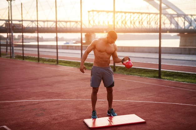 Knappe man aan het werk in de vroege ochtend met zonsopgang. fitness training buitenshuis.