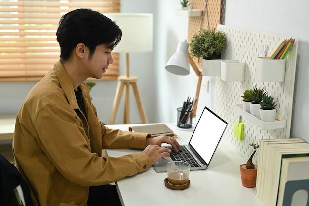 Knappe man aan het werk met een computerlaptop thuis.