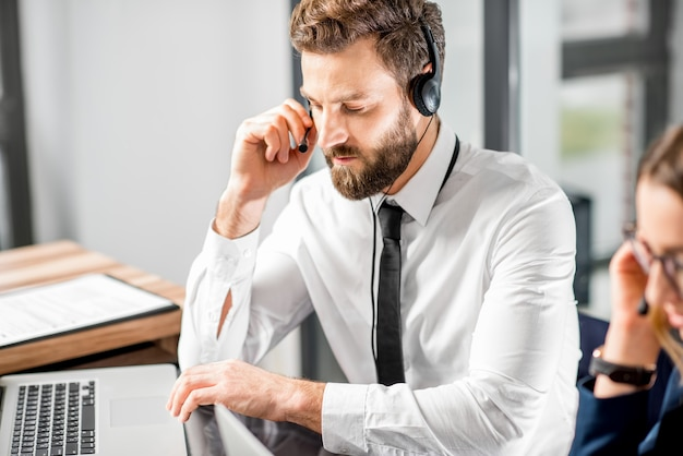 Knappe man aan het werk met headset en laptop in het callcenter