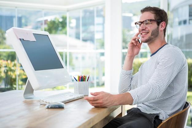 Knappe man aan het werk op computer en aan de telefoon in een heldere kantoor