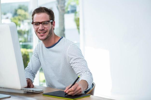 Knappe man aan het werk op computer in een heldere kantoor