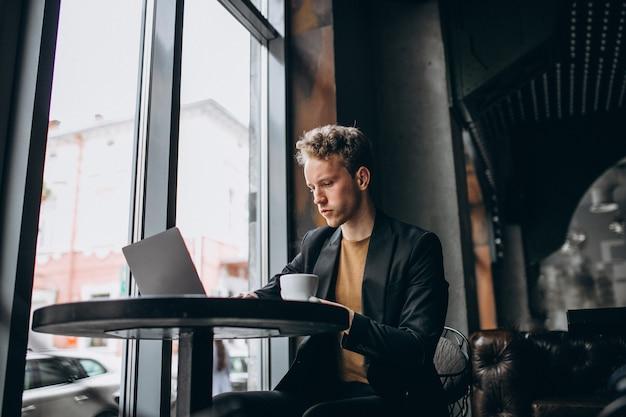 Knappe man aan het werk op een computer in een café en koffie drinken