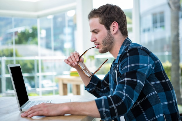 Knappe man aan het werk op laptop in een heldere kantoor