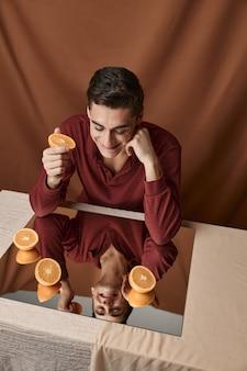 Knappe man aan tafel met sinaasappels op het bovenaanzicht van de spiegel. hoge kwaliteit foto
