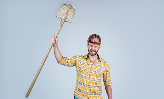 Knappe man aannemer in bouw veiligheidshelm en geruit hemd op bouwplaats met schop, dag van de arbeid.