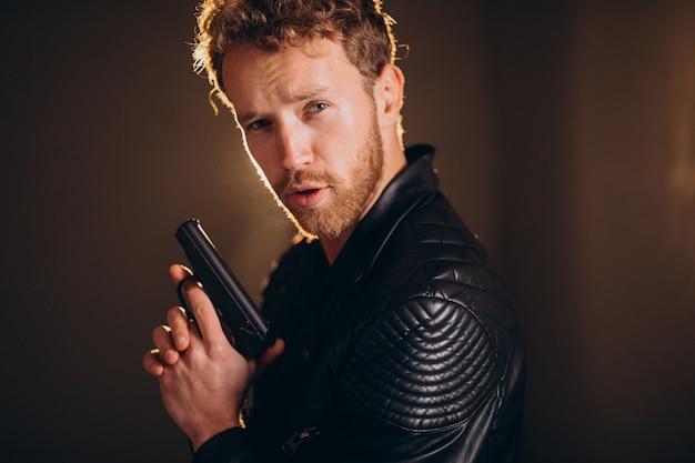 Knappe man acteur poseren in studio met wapen