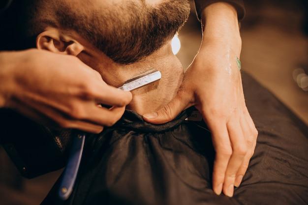 Knappe man baard scheren bij kapperszaak