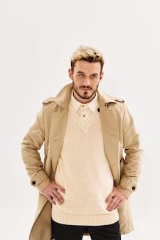 Knappe man beige jas handen aan de riem kijk vooruit modieus kapsel