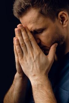 Knappe man bid en geloof in god. orthodox christelijk geloof. de mens bedekt zijn gezicht met zijn handen en denkt aan het leven