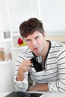 Knappe man blaast op zijn kopje koffie in de keuken zitten