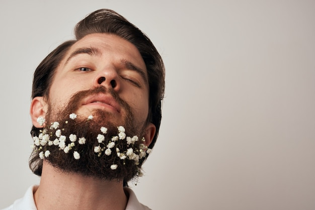 Knappe man bloemen in baard versieringen elegante stijl close-up.