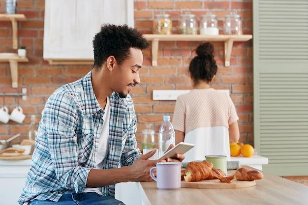 Knappe man brengt ochtend door in de keuken, ontbijten, leest elektronisch boek of teksten met vrienden met behulp van digitale tablet