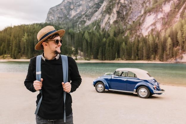 Knappe man chillen op de oever van het meer na een bezoek in de bergen en wegkijken genieten van de natuur