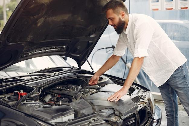 Knappe man controleert de motor in zijn auto