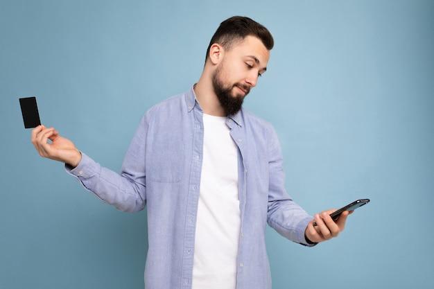 Knappe man die alledaagse kleding draagt, geïsoleerd op een achtergrondmuur, die telefoon en creditcard vasthoudt en gebruikt om te betalen terwijl hij naar het smartphonescherm kijkt,