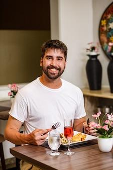 Knappe man die alleen in het restaurant dineert tijdens de pandemie
