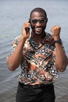 Knappe man die buiten aan de telefoon praat