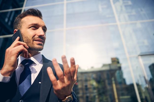 Knappe man die buiten in de buurt van een glazen gebouw blijft terwijl hij op een mobiele telefoon spreekt en er serieus uitziet