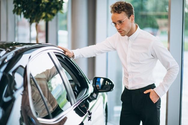 Knappe man die een auto in een showroom kiest