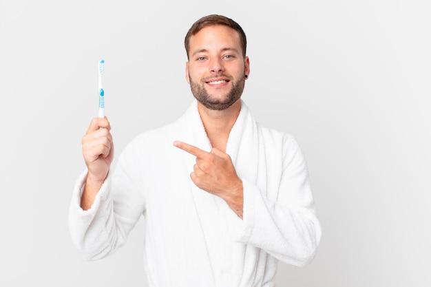 Knappe man die een badjas draagt en een tandenborstel vasthoudt