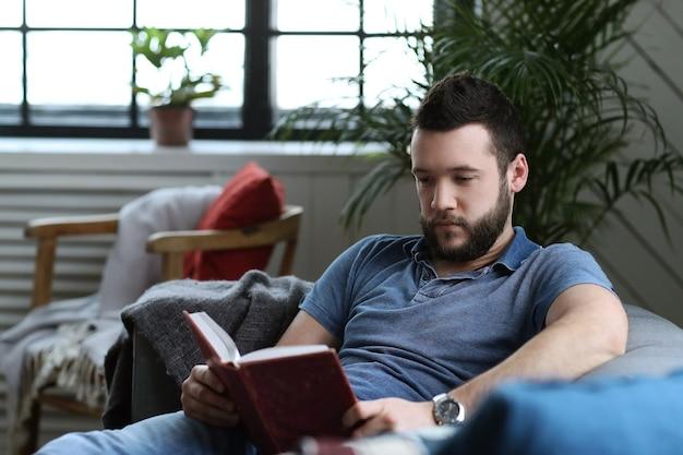 Knappe man die een boek leest in de bus