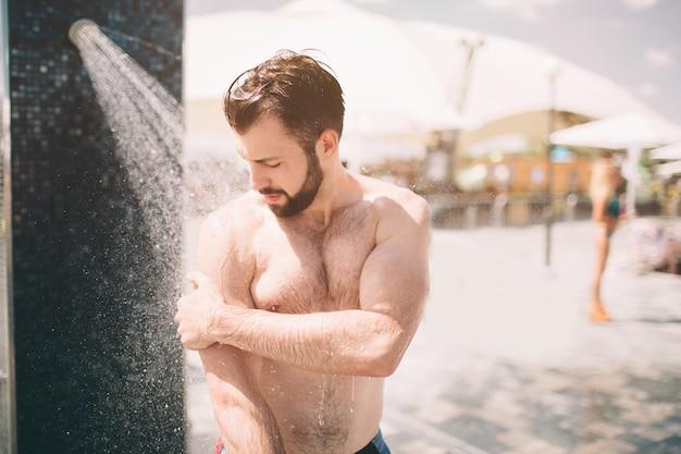 Knappe man die een douche nemen op het strand